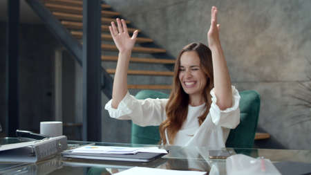 Close up young business woman getting excited with documents at remote office. Happy businesswoman relaxing after work with smile. Joyful girl dancing at workplace in slow motion. Banco de Imagens
