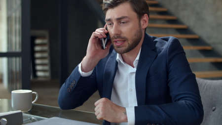 Portrait of angry businessman talking phone at home office emotionally. Closeup stressed business man calling on cell phone in slow motion. Frustrated man having problem on workplace.