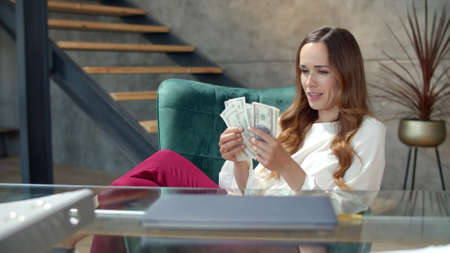 Joyful girl counting money cash in modern office. Successful businesswoman getting bundle of money in office. Happy business woman throwing cash money away in slow motion. Lady hitting jackpot Banco de Imagens
