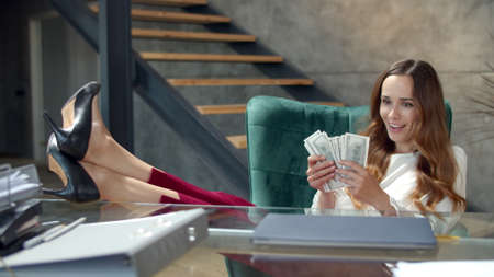 Portrait of happy businesswoman holding money cash with legs on table. Joyful business woman celebrating lottery win in office. Closeup attractive girl making money rain at office desk in slow motion. Banco de Imagens - 162270976