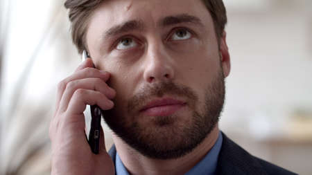 Portrait of young businessman talking phone at remote office. Focused man discussing on cellphone in slow motion. Closeup handsome guy calling mobile phone at home office.
