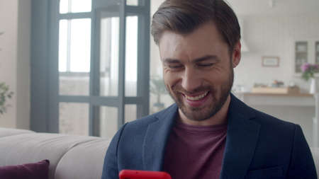 Closeup handsome business man laughing with phone at home. Portrait of smiling guy reading funny text on phone in flat. Joyful man surfing internet on smartphone on sofa. Guy reading funny email . Banco de Imagens