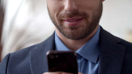 Closeup attractive businessman texting on cell phone at home office. Close up smiling man surfing internet on phone at home. Unrecognizible male person reading email on smartphone at remote workplace. Banco de Imagens