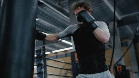 Closeup angry kickboxer hitting punching bag at gym. Wicked sportsman training kicks in sport club. Agitated fighter working on blows in fitness center.