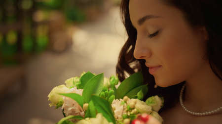 Portrait of brunette bride posing with flowers in garden. Calm woman holding flower bouquet in park. Closeup relaxed girl smelling flowers outdoors. Stok Fotoğraf