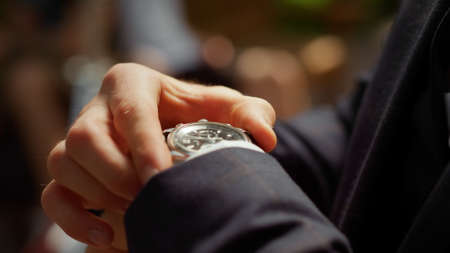 Closeup unrecognizable man looking at wrist watch in park. Male person in formal suit checking time outdoors. Unknown man getting better sleeve in garden. Guy hiding watch under sleeve Stok Fotoğraf