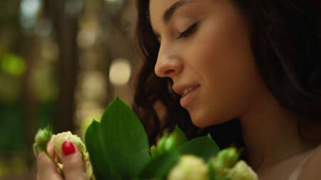 Romantic bride holding flowers in garden. Closeup charming woman touching leaves and flowers outdoors. Portrait of brunette girl smelling roses in park.