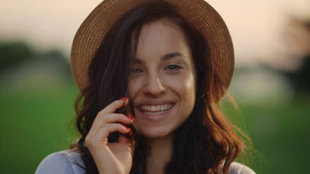 Portrait of playful girl face smiling at sunset outdoors. Closeup happy woman having rest at weekend in summer park. Young girl flirting with camera in park. Smiling woman posing at field