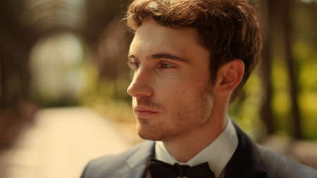 Portrait of romantic groom looking at camera under arch. Handsome guy waiting for ceremony outdoors. Closeup playful man flirting in park.