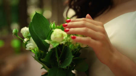 Woman hands touching bouquet in park. Portrait of gorgeous girl smelling roses outdoors. Closeup charming bride standing with flowers in garden. Stok Fotoğraf