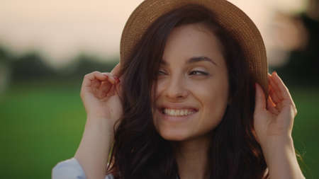 Closeup smiling woman wearing straw hat outdoors. Portrait of joyful lady having rest at weekend in summer park. Brunette girl face posing on field at sunset. Cute female person spending time in park Stok Fotoğraf