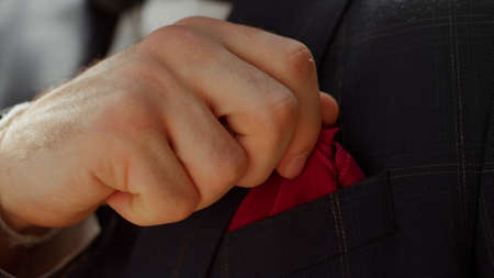 Unrecognizable man getting ready for wedding ceremony outdoors. Closeup man hands preparing for event in park. Male person touching handkerchief in garden. Man getting better jacket