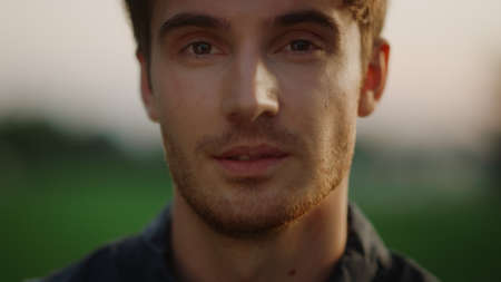 Closeup handsome man looking at camera outdoors at sunset. Cheerful model guy staring at camera with smile in summer park. Portrait of attractive male person smiling on meadow. Stok Fotoğraf