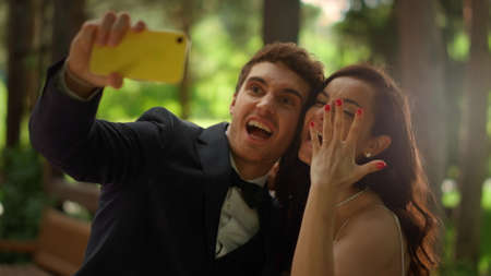 Portrait of playful man and woman doing selfie photo on mobile phone outdoors. Closeup joyful wedding couple making hand gestures in park. Handsome groom doing facial expression in garden.