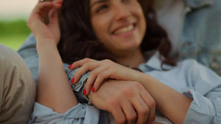 Portrait of cute couple spending time on picnic in summer park. Closeup attractive man touching woman hair on romantic date outdoors. Charming girl laughing while lying on guy in park.