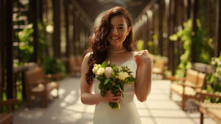 Happy girl waiting for wedding ceremony outdoors. Romantic bride posing with flower bouquet under arch in park. Portrait of smiling woman looking camera in restaurant.