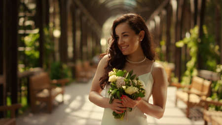 Portrait of smiling woman waiting for wedding ceremony in park. Closeup happy girl posing in wedding dress outdoors. Charming bride feeling happy with bouquet under arch in park.