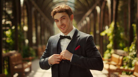 Portrait of smiling man buttoning up jacket in park. Closeup worried groom preparing to wedding ceremony outdoors. Attractive male person posing under arch in garden.