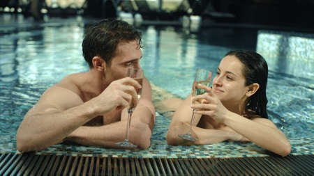 Portrait of cute couple lying in thermal pool in spa background. Closeup beautiful guy and girl drinking champagne in pool indoor. Smiling man and woman looking at each other in pool inside