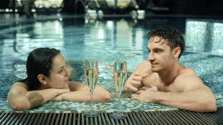 Portrait of sweet couple talking in swimming pool indoors. Closeup handsome guy and pretty girl chilling in luxury spa. Young man and woman looking each other in spa pool inside. Stok Fotoğraf