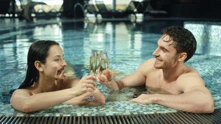 Closeup beautiful man and woman clinking glasses in spa pool indoors. Portrait of romantic couple enjoying vacation in luxury spa background. Happy guy and girl flirting in pool inside.