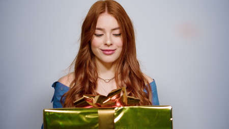 Closeup excited woman holding gift on gray background. Portrait of smiling female person shaking present box indoors. Surprised girl trying to guess box content in studio.