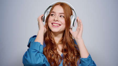 Portrait of relaxed woman making movements in studio. Closeup calm female person wearing headphones on gray background. Smiling girl listening music indoors.