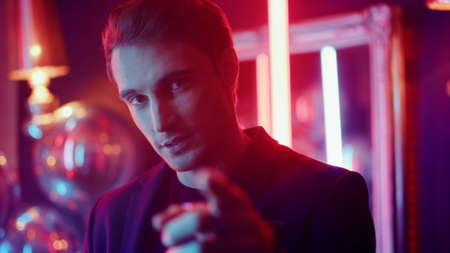 Closeup sexy guy flirting with camera on neon lights background. Portrait of young male person pointing with finger in nightclub. Hot man raising glass at party in club. Banco de Imagens - 158042664