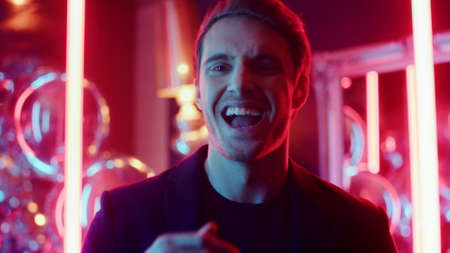 Cheerful man looking at camera at club party. Portrait of positive male person laughing on neon lights background. Closeup joyful guy smiling in nightclub.