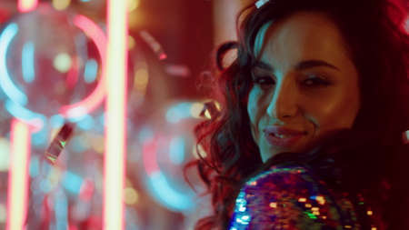 Closeup happy girl moving body in nightclub. Portrait of female person spending time at night club party. Playful woman dancing on neon lamps background in slow motion. Banco de Imagens