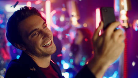 Closeup candid guy using phone in nightclub. Portrait of natural male person chatting video on neon lights background. Emotional man having video call at party in night club. Banco de Imagens - 158042353