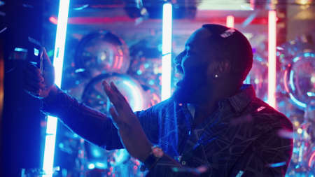 Portrait of smiling male person doing selfie photo on neon lamps background. Closeup afro man showing victory sign under confetti in slow motion. African american man making photos at night club party Banco de Imagens