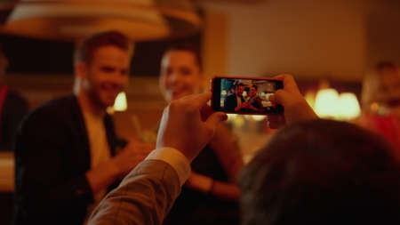 Happy friends posing for photo on smartphone in bar. Smiling couple photographing on mobile phone with cocktails in luxury restaurant at evening. Joyful people having rest in nightclub party.