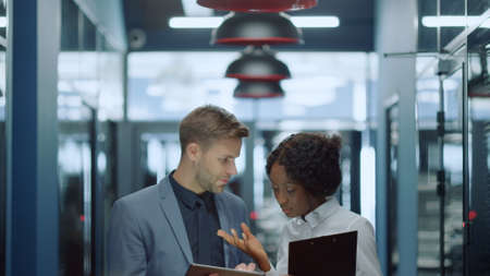 Smiling multiracial business couple dicussing work in corridor. Young man and woman talking about project in business center. Portrait of young professionals scrolling tablet in hallway Banco de Imagens