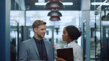 Portrait of multi ethnic colleagues having discussion in corridor. Smiling man and woman talking about business plan in office. Positive business couple working in business center hallway.