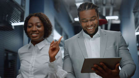 Closeup african american colleagues walking in business center. Positive afro business couple discussing plan on tablet computer in office. Successful business people working on the go in corridor