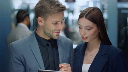 Business colleagues talking about corporate plan in business center. Portrait of cheerful man and woman using tablet computer in corridor. Closeup smiling business couple discussing project in office Banco de Imagens - 158348959