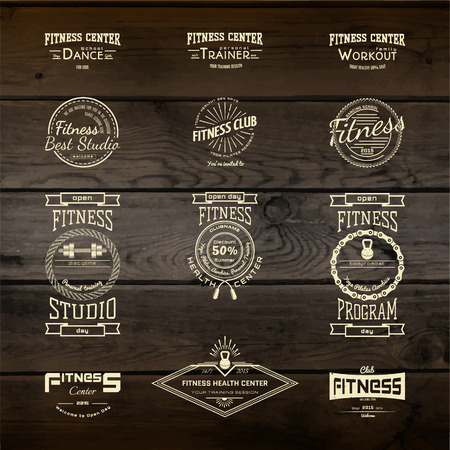 Fitness club badges logos and labels for any use, on wooden background texture
