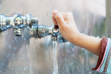 Child's hand with drinking water running from tap water Standard-Bild