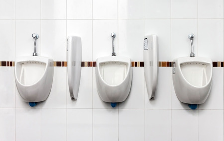 A row of urinals in tiled wall in a public restroom  photo