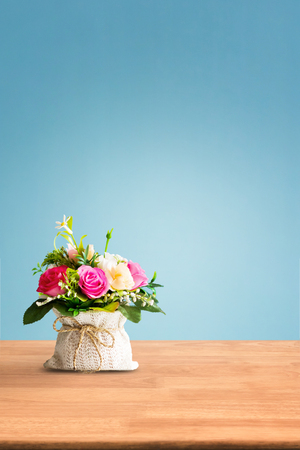 Artificial flowers on table with blue background
