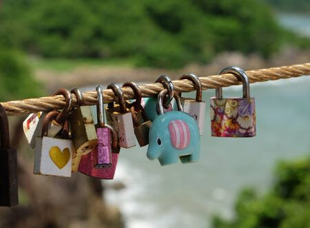 The Color love padlock locked on rope bridge bridge. Symbol of marriage and eternal love.Belief of people that their love will be as strong as pair of lock which still there from time to time. Stockfoto
