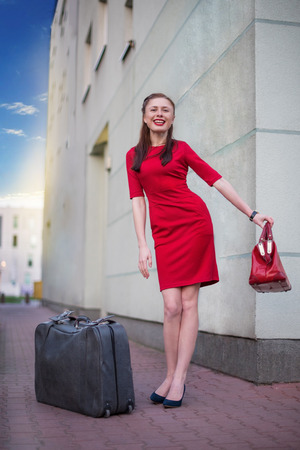 valise: Girl with gray vintage case in the city. She travel with this valise in her red dress.