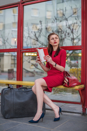 valise: Girl with gray vintage case on yhe bus-stop. She travel with this valise in her red dress.