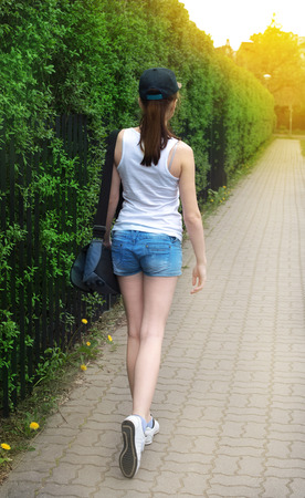 brixton: strolling girl in blue cap with green nature on background
