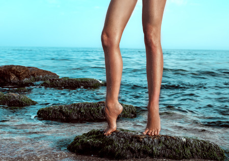 Womans legs at beach jetty Stock Photo
