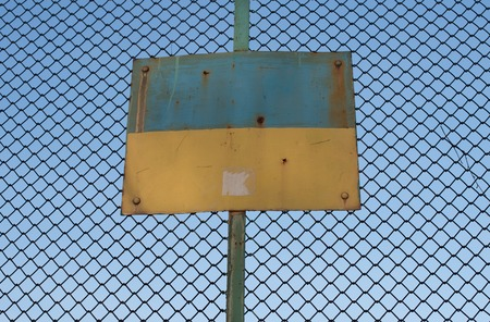 iron fence: Old Rusty Ukrainian flag depicted on the plaque attached to the iron fence Stock Photo