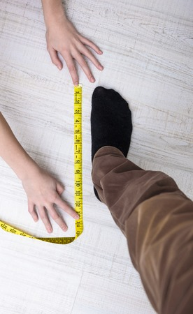 measures: girl measures the size of your male legs Stock Photo