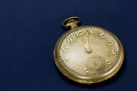 old and dirty golden pocket watch on blue background photo