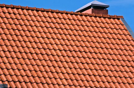 chimney corner: Red tiles and chimney on a house roof Stock Photo